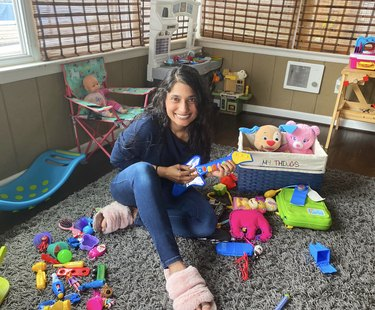 photo of Mamta Patel Nagaraja in playroom holding toy guitar