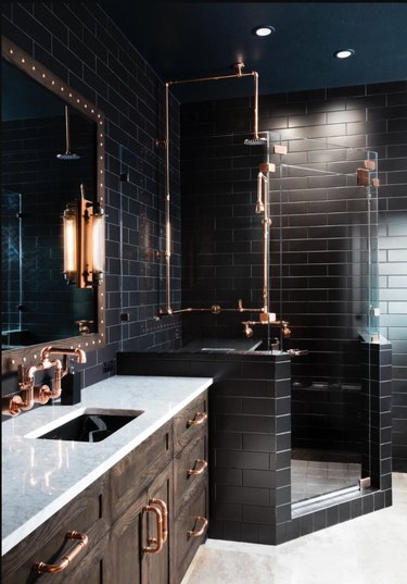 black bathroom with copper hardware