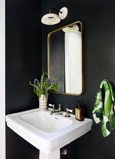black bathroom with pedestal sink and white sconce above brass mirror