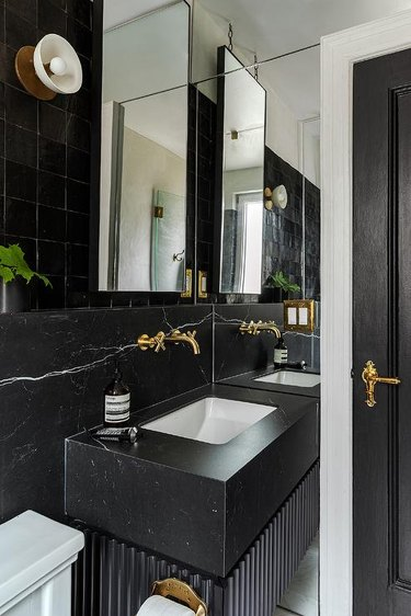 all black bathroom with gold hardware