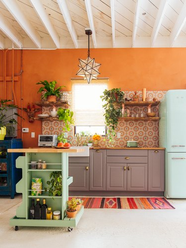 mint green kitchen cart in orange and white bohemian kitchen