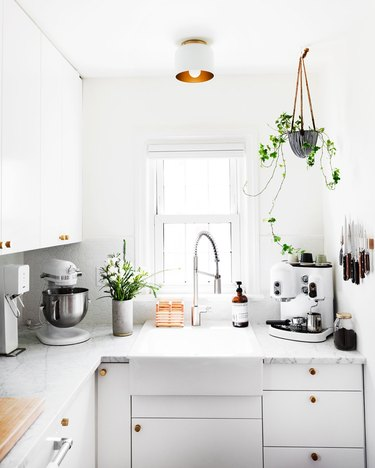 white kitchen with flush mount ceiling light above sink