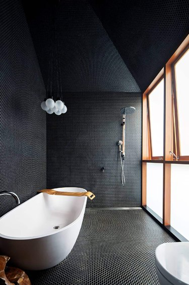 modern black bathroom with penny tile and freestanding tub