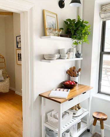 white kitchen cart with wood top alongside white floating shelves