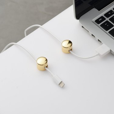 brass button cord keepers on white desk
