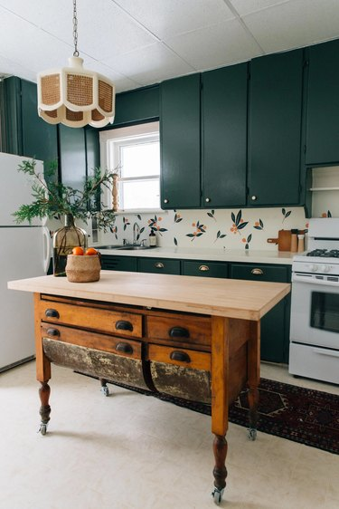 vintage style kitchen cart in kitchen with teal cabinets