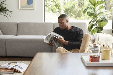 person sitting near couch and coffee table