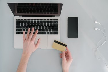 laptop and hand holding credit card