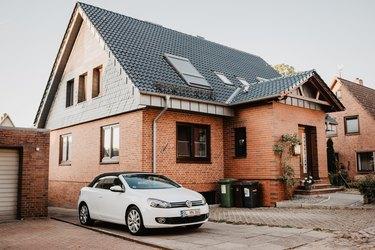 brick house and white car