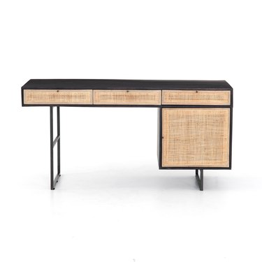 cane front desk with black trim and drawers for storage