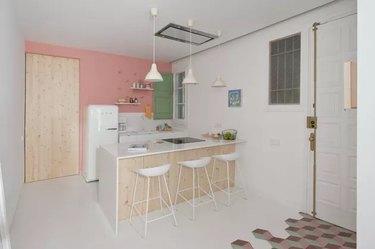 modern kitchen with bubblegum pink walls and smeg fridge