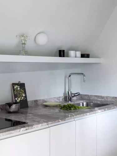 light blue kitchenette with gray marble counters