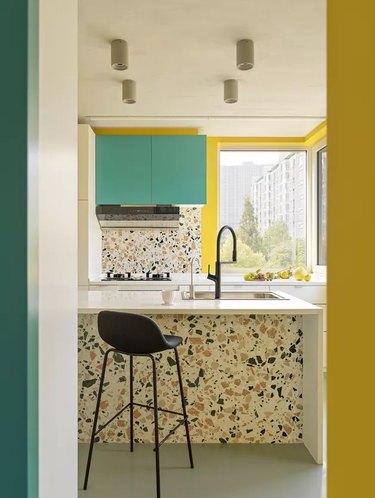 bright contemporary kitchen with terrazzo and yellow walls