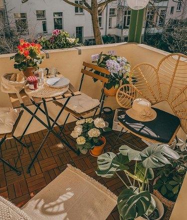 bistro set on balcony with flowers