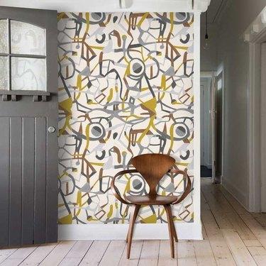 Entryway with modern wallpaper, wood floors, modern chair, gray door.
