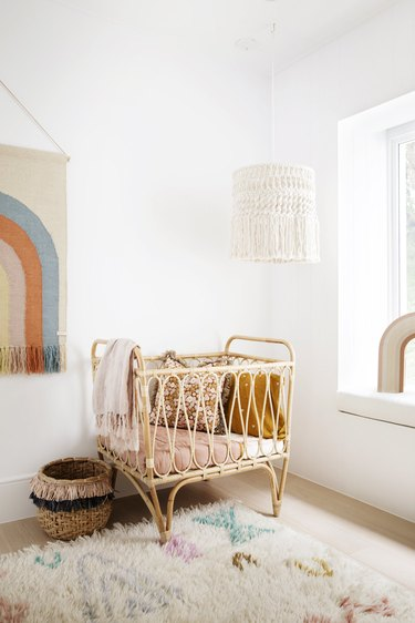bohemian nursery with rattan crib and rainbow wall hanging