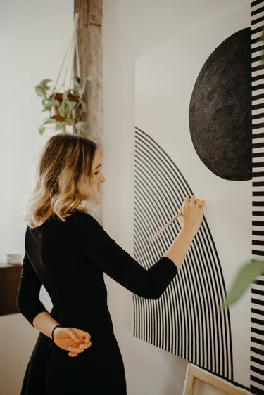 Sofia Shu painting canvas in art studio