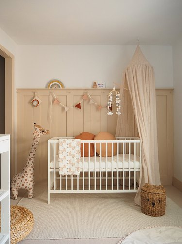 gender neutral nursery with pinkish nude wall panelling and cuddly giraffe
