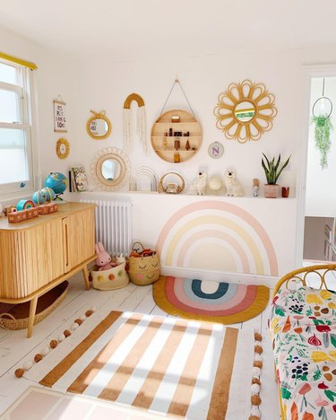colorful nursery with hand painted rainbow wall mural
