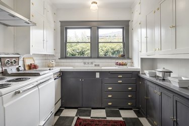 craftsman kitchen with two tone cabinets in gray and white and checkerboard floor