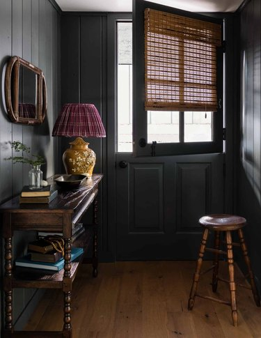 Entryway with dark gray paint, console table, stool, wood floors.