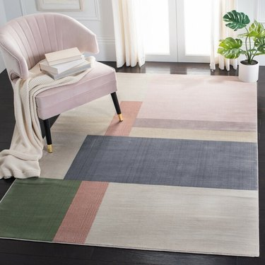 seating area with plant and pink chair with multicolored rug