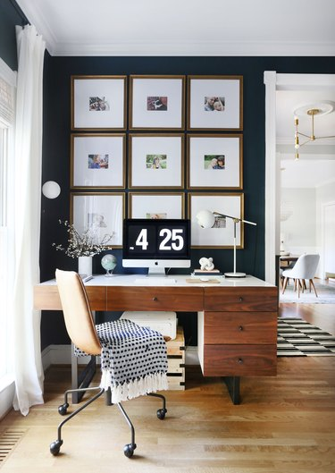 corner home office with gallery wall and wood desk