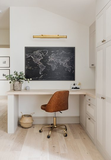 corner home office with built-in desk and leather office chair