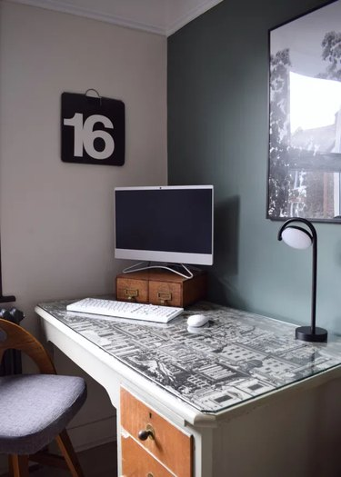 corner home office with green accent wall and minimalist decor