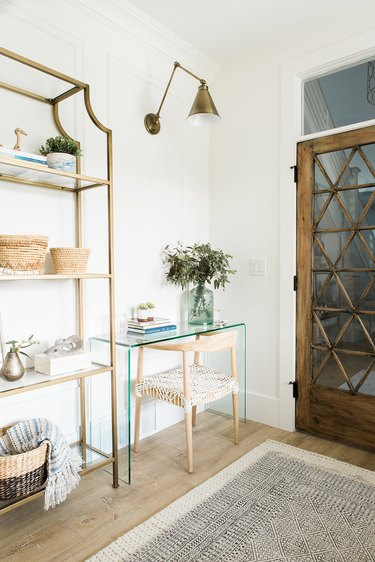 corner home office with glass desk and brass wall sconce