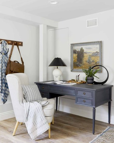 corner home office with vintage blue desk and upholstered office chair