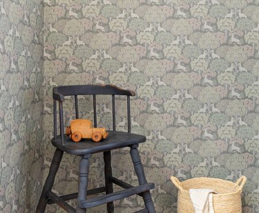 black chair with toy near basket and patterned wallpaper