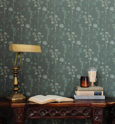 desk with lamp and books and candles near patterned wallpaper