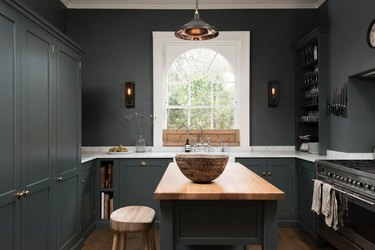 dark gray kitchen with white countertops and wood floor