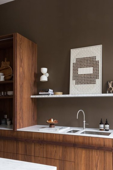 brown kitchen walls with wood cabinetry and slim marble countertop