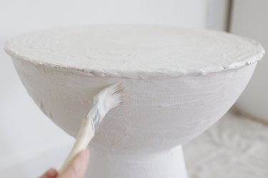 Brushing last layer of plaster with a wet paintbrush