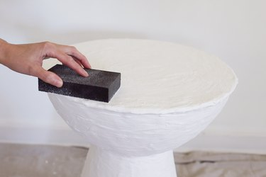 Sanding rough spots on dried plaster with a sanding sponge