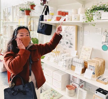 Alice Chen has dark hair and wears a red jacket with an orange face mask while pointing to her candles in a boutique.