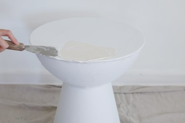 Applying first coat of plaster to table with a putty knife