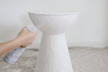 Spraying plastered table with clear sealant topcoat