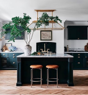 Kitchen with black and marble kitchen island and large plant