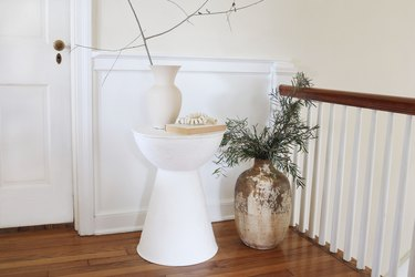 DIY plaster side table styled with vase, branches and book