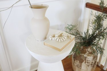 DIY plaster side table styled with vase and book