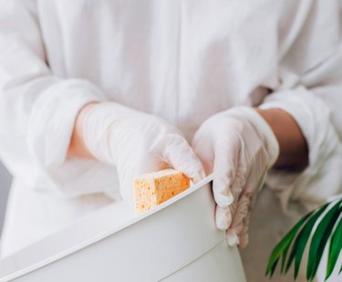 Cleaning white garbage can with sponge