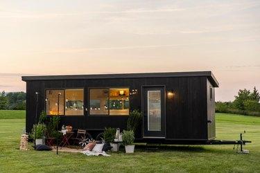 IKEA black tiny house in grassy area