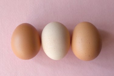 two brown eggs and one white egg over pink background