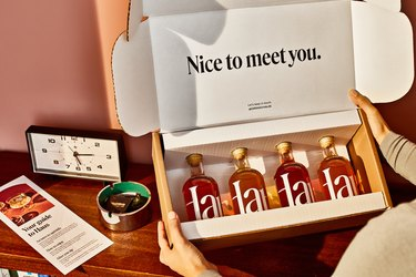 "table with clock and box that says ""nice to meet you"" with bottles inside being held by a person"