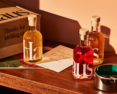 table with three bottles of spirits next to box and dish