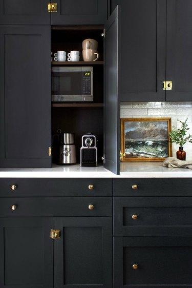 modern black kitchen with appliance garage housing espresso machine, milk frother, toaster, small microwave and blender.