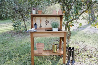 DIY cane webbing potting bench with garden tools and terra cotta pots